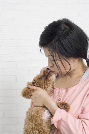 Young woman kissing pet dog