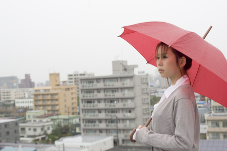 Young woman with umbrella LANG_EVOIMAGES