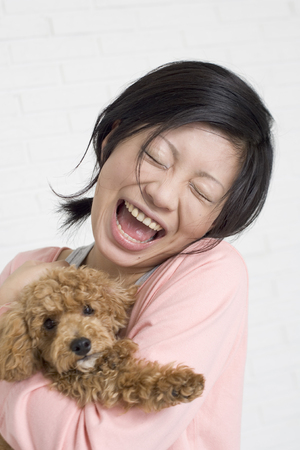Woman holding pet dog LANG_EVOIMAGES