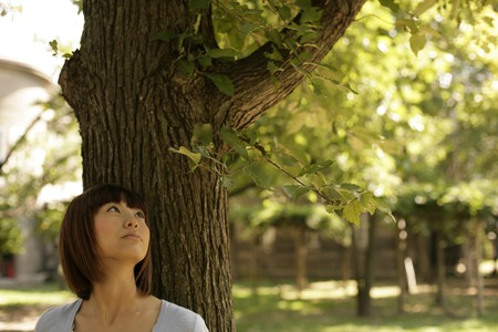 Young woman leaning against tree LANG_EVOIMAGES