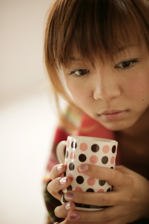 comfort food: Young woman holding cup