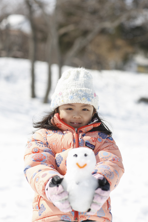 give out: A girl holding a small snowman