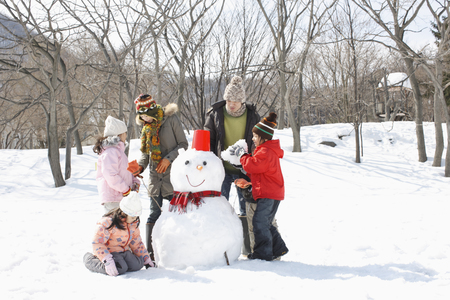 Family making a snowman LANG_EVOIMAGES