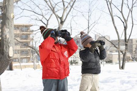 Children peering through binoculars