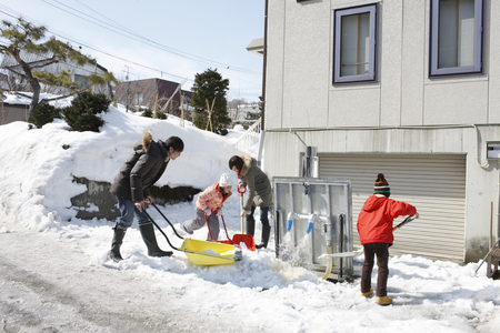 Family removing snow