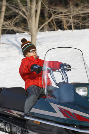 A boy riding on snowmobile LANG_EVOIMAGES