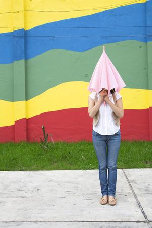Young woman hiding in umbrella