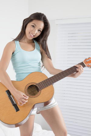 Young woman playing the guitar