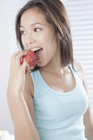 Young woman biting an apple LANG_EVOIMAGES