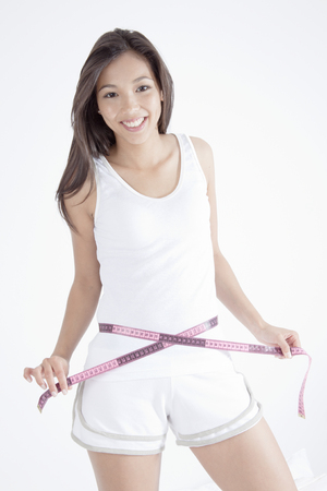 Young woman measuring waist with tape LANG_EVOIMAGES