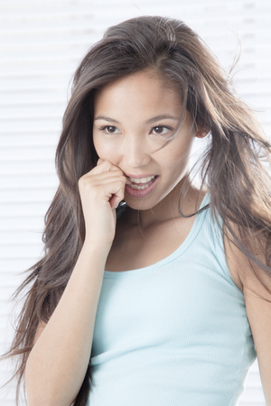 Young woman biting finger