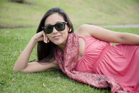 Woman with sunglasses lying on grass LANG_EVOIMAGES