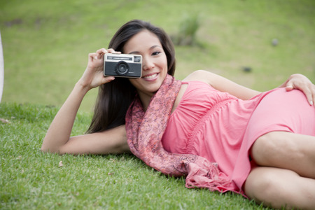 Young woman lying on grass and taking photo with camera LANG_EVOIMAGES
