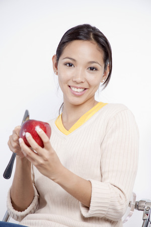 Young woman peeling an apple LANG_EVOIMAGES