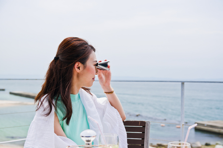 Woman looking into the distance through opera glasses LANG_EVOIMAGES