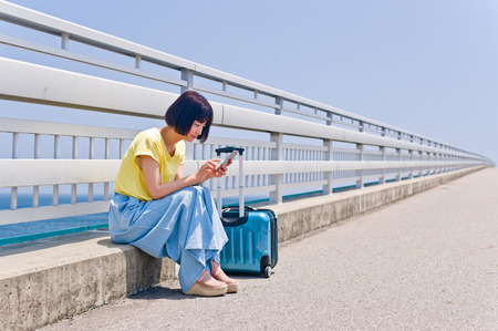 Woman sitting and operating smart phone LANG_EVOIMAGES