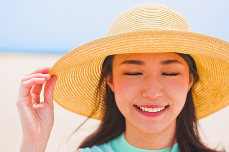 Woman wearing a hat at the seashore LANG_EVOIMAGES