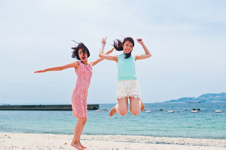 Two women jumping on the sandy beach LANG_EVOIMAGES
