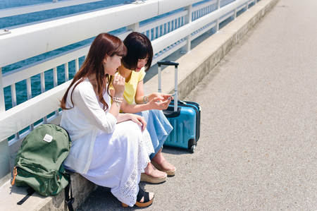 Women talking and seeing smart phone
