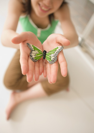 Woman holding out butterfly toy LANG_EVOIMAGES