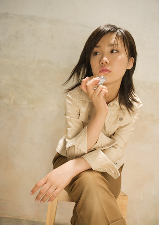 Young woman sitting on chair LANG_EVOIMAGES