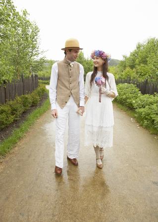 Walking bridal couple holding hands LANG_EVOIMAGES