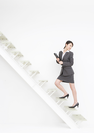 Business woman walking up the stairs LANG_EVOIMAGES
