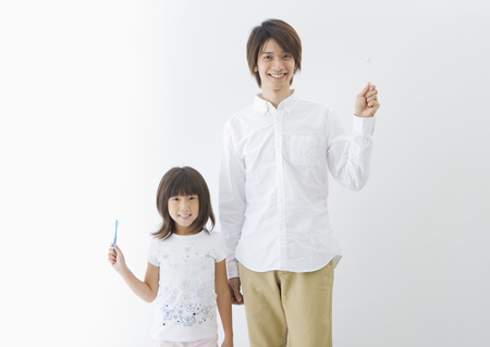 Father and daughter holding toothbrushes LANG_EVOIMAGES