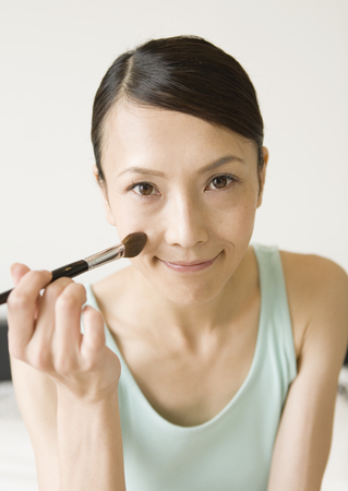 A woman having makeup on LANG_EVOIMAGES