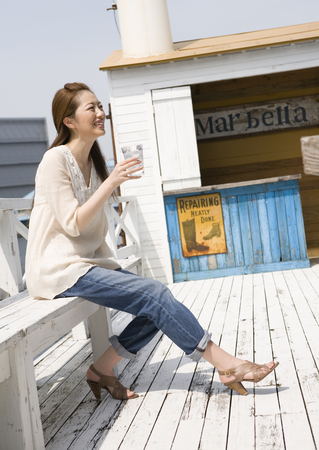 Young woman relaxing on wood deck LANG_EVOIMAGES