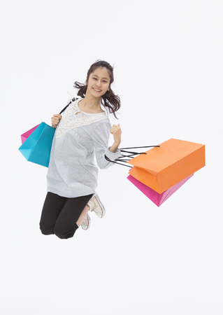 Young woman holding shopping bags LANG_EVOIMAGES
