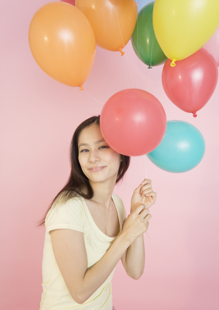 Young woman holding balloons