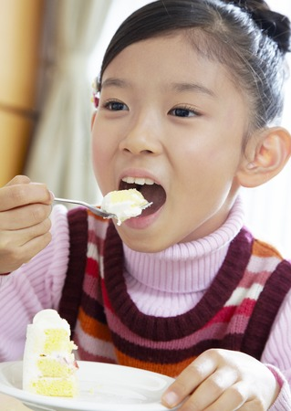 Girl eating cake LANG_EVOIMAGES