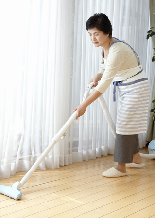 Woman vacuuming LANG_EVOIMAGES