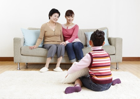 Three-generation family relaxing in room