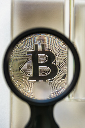 Bitcoin metal crypto coin under glass prism and magnifying glass Imagens