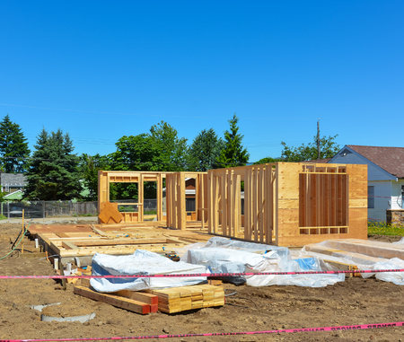Single family home under construction on blue sky background.