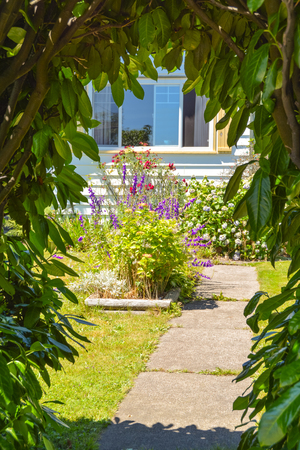 Look through the green gate on the pathway leading to a house with flowers on the front yard