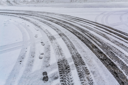 Car tire traces on the snow with human steps traces beside