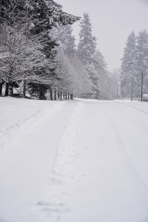 Snowy winter road with tire traces on the snow and cleaned walkway on the side