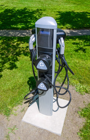 EV charger on green grass lawn. EV - electric vehicle charging station. Electric car charging point.