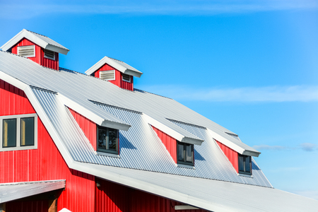 Top roof of new red barn on blue sky background