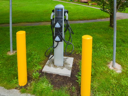 EV charger on green grass lawn. EV - electric vehicle charging station. Electric car charging point with yellow pillars around.