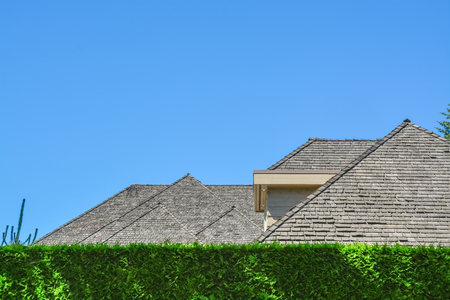 Residential house with massive roofs, green hedge in front on blue sky background. Family house with big roofs tiled by wooden shingles Banque d'images
