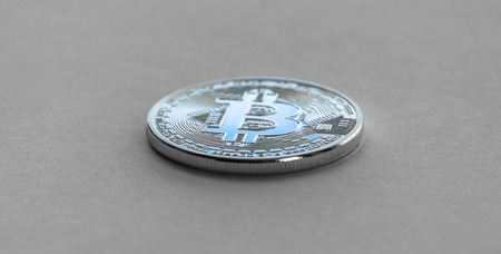 Bitcoin laying on flat surface. White metal coin Zdjęcie Seryjne