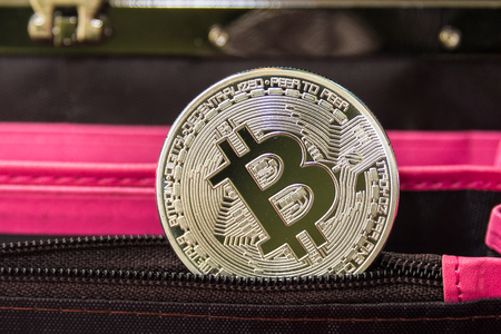Bitcoin metal coin laying on black leather wallet