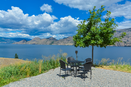 Picnic area with dining table and chairs and lonely tree on high shore. Panoramic overview of Okanagan lake