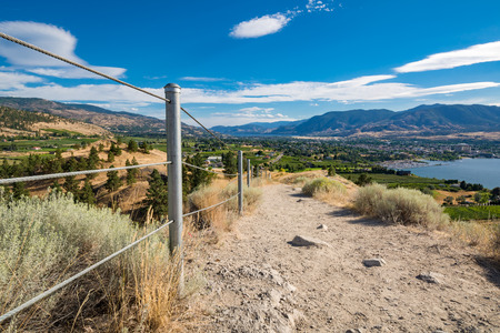 Panoramic view over valley with a city between lakes. Gravel trail leading towards the town downhill