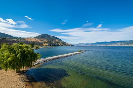 Magnificent view over Okanagan lake and valley with narrow foreland and clouds over blue sky 版權商用圖片 - 122885596