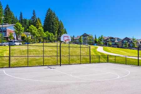 Basketball court within big park area in residential neighborhood